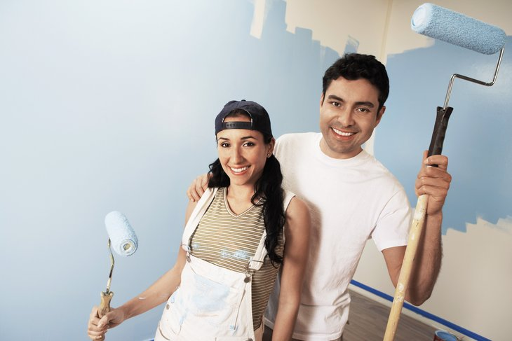 Couple painting a room in their home