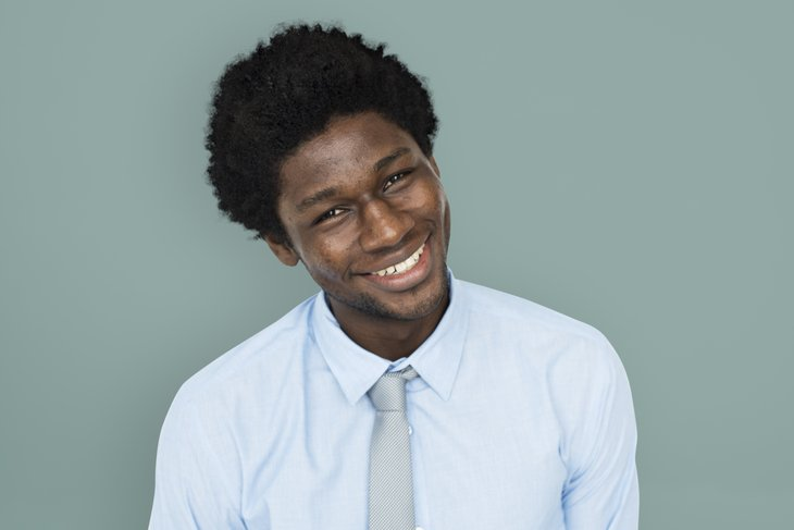 Young African American man with head tilted, smiling.