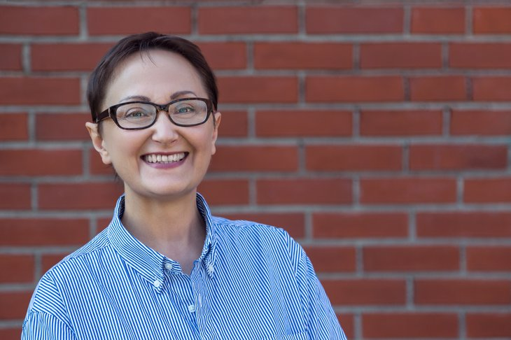 Older woman smiling, brick wall in background.