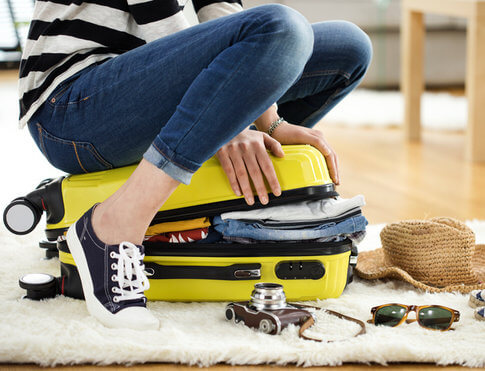 Girl with yellow suitcase packing for trip and preparing her apartment