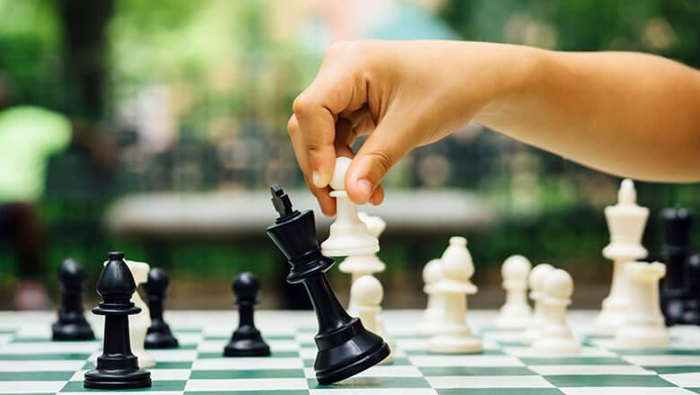 child's hand playing chess